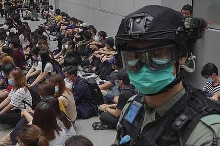 Von Bereitschaftspolizisten festgehaltene regierungskritische Demonstranten im Zentrum von Hongkong. Foto: Vincent Yu/AP/dpa