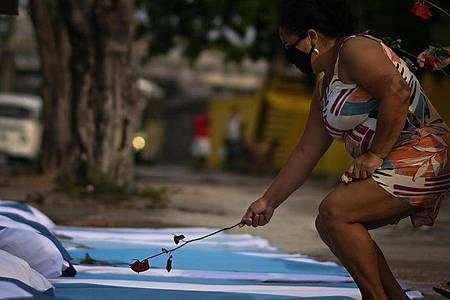 Im Gedenken an die rund 300.000 Corona-Toten in Brasilien legt eine Frau eine Rose ab. Foto: Andre Borges/dpa