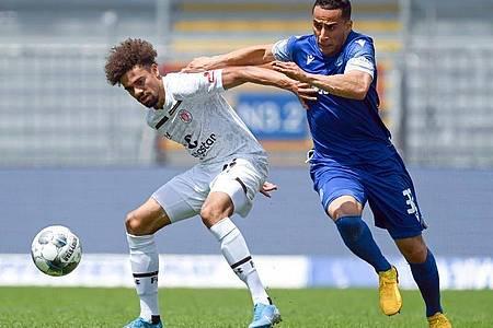 Luis Coordes (l) vom FC St. Pauli schirmt den Ball gegen Änis Ben-Hatira ab. Foto: Matthias Hangst/Getty Images Europe/Pool/dpa