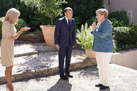 Emmanuel Macron, Präsident von Frankreich, begrüßt neben seiner Frau Brigitte (l) Bundeskanzlerin Angela Merkel (CDU), bei ihrer Ankunft in der Sommerresidenz des Staatschefs, dem Fort de Bregancon. Foto: Michael Kappeler/dpa