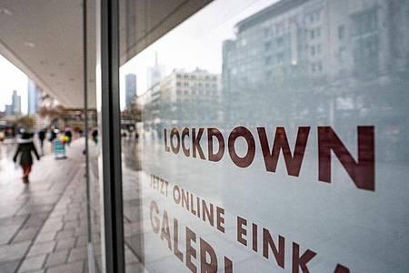 «Lockdown» steht im Schaufenster eines geschlossenen Kaufhauses, das darunter zum Online-Einkauf rät. Foto: Frank Rumpenhorst/dpa