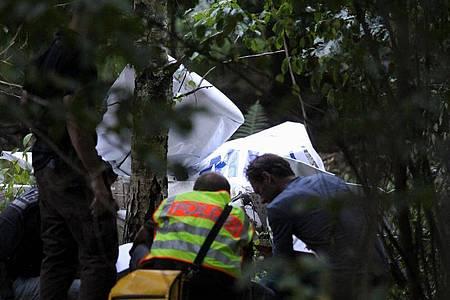 Einsatzkräfte der Polizei stehen am Wrack eines der abgestürzten Ultraleichtflugzeuge. Foto: Thomas Riedel/dpa