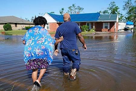 Zwei Menschen gehen durch eine überflutete Straße in Lake Charles (Louisiana). Foto: Gerald Herbert/AP/dpa