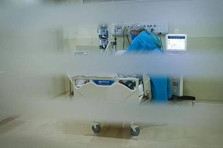 Eine medizinische Mitarbeiterin behandelt einen Patienten im Krankenhaus. Foto: Lincon Zarbietti/dpa