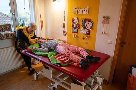 Margret Pohl, Kinderärztin und Vorsitzende des Vereins für Körper- und Mehrfachbehinderte Mainz, steht in ihrem Wohnhaus an der Liege, auf der ihre Tochter Ella Franziska liegt. Foto: Frank Rumpenhorst/dpa