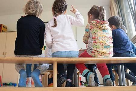Kinder sitzen in einem Kindergarten dicht auf einer Bank nebeneinander. Foto: Sebastian Kahnert/dpa-Zentralbild/dpa