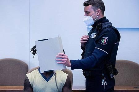 Der Angeklagte wird in Handschellen in einen Gerichtssaal im Landgericht Köln geführt. Foto: Rolf Vennenbernd/dpa