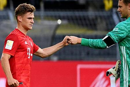 Joshua Kimmich (l) und Torwart Manuel Neuer grüßen sich mit der Faust. Foto: Federico Gambarini/dpa-Pool/dpa