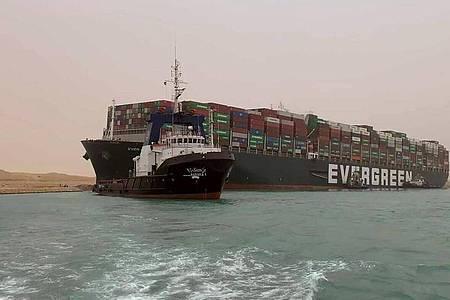 Ein Schlepper zieht die «Ever Green». Das Frachtschiff ist in der Nacht zum 24. März auf Grund gelaufen und blockierte seither die wichtiges Schifffahrtsstraße zwischen Asien und Europa. Foto: Uncredited/Suez Canal Authority/AP/dpa