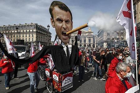 Demonstranten ziehen mit einem Zigarre rauchenden Abbild des französischen Präsidenten Macron durch Paris. Foto: Michel Euler/AP/dpa
