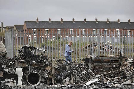 Ein Mann geht an einem ausgebrannten Bus auf der Shankill Road in West Belfast vorbei. Foto: Peter Morrison/AP/dpa