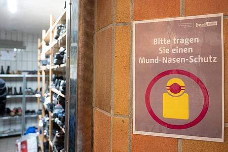 In der Kleiderkammer der Berliner Stadtmission hängt ein Plakat mit der Aufschrift ?Bitte tragen Sie einen Mund-Nasen-Schutz?. Foto: Christophe Gateau/dpa