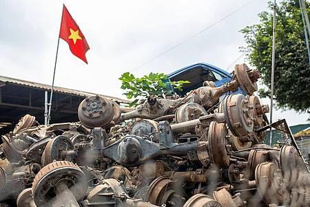 Die Flagge Vietnams weht in Te Lo über einem Haufen rostiger Autoachsen, dahinter steht eine leere LKW-Kabine. Foto: Chris Humphrey/dpa
