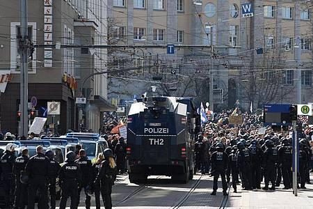 Einsatzkräfte der Polizei stehen bei einer Kundgebung unter dem Motto «Freie Bürger Kassel - Grundrechte und Demokratie» neben einem Wasserwerfer. Foto: Swen Pförtner/dpa