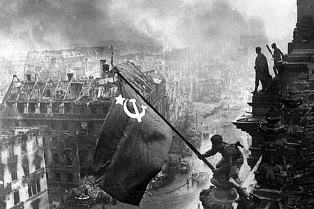 Der sowjetische Soldat Militon Kantarija aus Georgien hisst am 2. Mai 1945 die sowjetische Flagge auf dem Berliner Reichstag. Foto: Jewgeni Chaldej/Tass/dpa