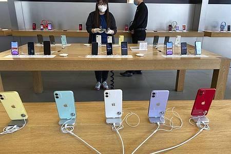 Mitarbeiter mit Mundschutz arbeitet in einem Apple Store in Peking. Foto: Ng Han Guan/AP/dpa