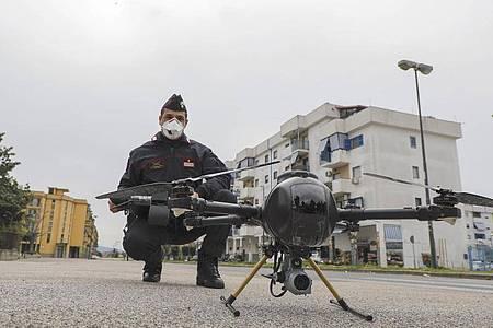 Ein Offizier der Carabinieri manövriert im Stadtviertel Scampia, Neapel, eine Drohne, um die Bewegungen der Menschen zu kontrollieren. (Archivbild). Foto: Fabio Sasso/LaPresse/dpa