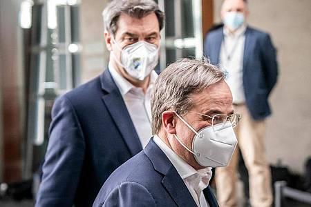 Markus Söder (hinten), Ministerpräsident von Bayern und CSU-Vorsitzender, kommt neben Armin Laschet, CDU-Bundesvorsitzender und Ministerpräsident von Nordrhein-Westfalen, zu einer Pressekonferenz. Foto: Michael Kappeler/dpa