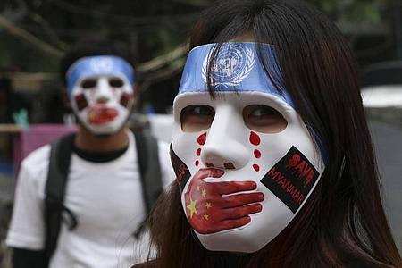 """Junge Demonstranten tragen Masken, auf denen das Logo der Vereinten Nationen, eine rote Hand über dem Mund, rote Tränen und Aufkleber mit der Aufschrift """"Save Myanmar"""" zu sehen ist. Foto: Uncredited/AP/dpa"""