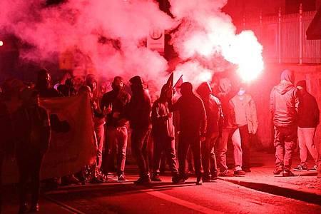 Teilnehmer der Demonstration unter dem Motto «Kämpfe verbinden - Für eine solidarische Nachbar*innenschaft» ziehen mit roten Pyro-Fackeln durch den Leipziger Stadtteil Connewitz. Foto: Hendrik Schmidt/dpa-Zentralbild/dpa
