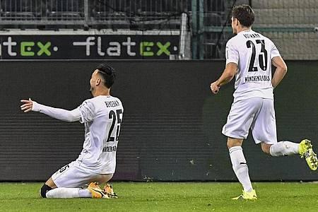 Mönchengladbachs Ramy Bensebaini (l) jubelt über sein Tor zum 3:2 gegen den BVB. Foto: Martin Meissner/Pool AP/dpa