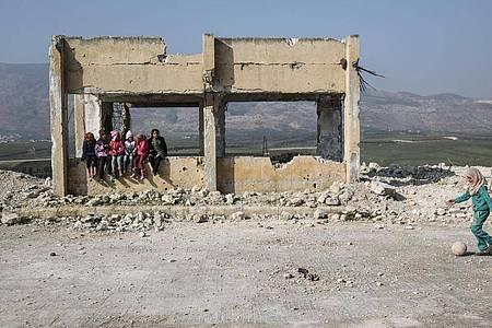 Kinder spielen in den Trümmern einer zerstörten Schule. Foto: Anas Alkharboutli/dpa