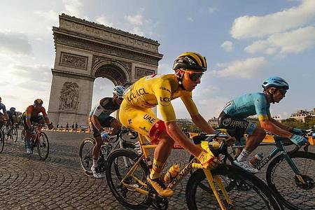 Der Slowene und Gesamtsieger Tadej Pogacar (M), der das gelbe Trikot des Gesamtführenden trägt, fährt am Arc de Triomphe vorbei. Foto: Christophe Ena/AP/dpa