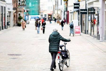 Eine Frau schiebt ihr Fahrrad durch die wenig belebte Fußgängerzone in Oldenburg. Angesichts stark steigender Infektionszahlen wird der Lockdown in Deutschland verlängert. Foto: Hauke-Christian Dittrich/dpa