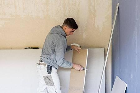 Die Arbeit von Stuckateuren fordert auch körperlich. Azubi Jonas Schwarzwälder schneidet ein Trockenbauelement zu. Foto: Philipp von Ditfurth/dpa-tmn