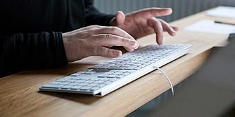 Mann tippt auf einer PC-Tastatur