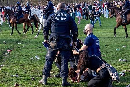 Polizist im Einsatz im Park Bois de La Cambre. Die Sicherheitskräfte wurden aus der teils sehr aggressiven Menschenmenge heraus mit Flaschen beworfen. Foto: Hatim Kaghat/BELGA/dpa