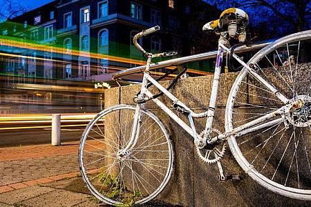 Fahrzeuge fahren an einem sogenannten «Ghost Bike» vorbei, welches an einer Kreuzung in Hannover an einen tödlich verunglückten Fahrradfahrer erinnert. Foto: Moritz Frankenberg/dpa