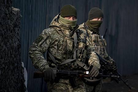 Ukrainische Soldaten an einem Kontrollpunkt unweit einer von Separatisten kontrollierten Region. Foto: Evgeniy Maloletka/AP/dpa