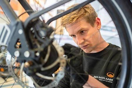 Im Februar hat er seine Ausbildung zum Zweiradmechatroniker abgeschlossen: Stefan Borschert setzt ein neues Hinterrad an einem E-Lastenrad ein. Foto: Nicolas Armer/dpa-tmn
