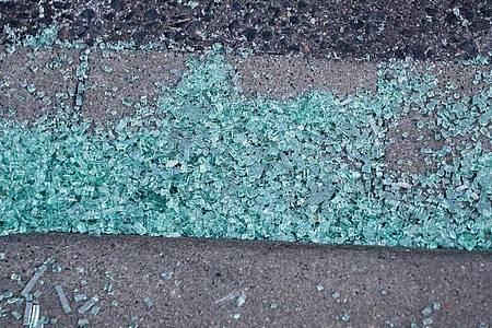 Glasscherben einer Autoscheibe liegen auf einem Gehweg. Die Hintergründe der Attacke blieben zunächst offen. Foto: David Young/dpa
