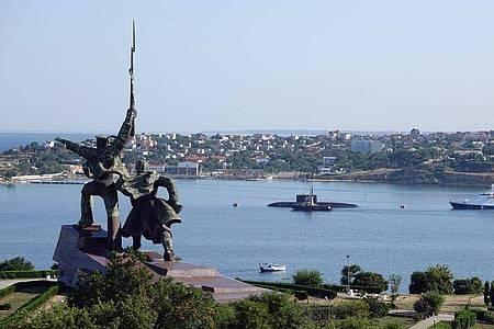 Hinter dem sowjetischen Denkmal «Soldat und Seemann» liegen ein U-Boot und Kriegsschiffe der russischen Schwarzmeerflotte vor Anker in der Hafenstadt Sewastopol. Foto: Ulf Mauder/dpa