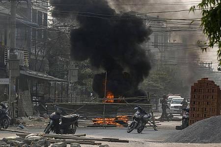 Bewaffnete Polizisten und Soldaten aus Myanmar erreichen eine Barrikade, die von Putschgegnern in Mandalay errichtet wurde. In vielen Städten gibt es weiterhin Proteste gegen die Militär-Junta im Land. Foto: Uncredited/AP/dpa