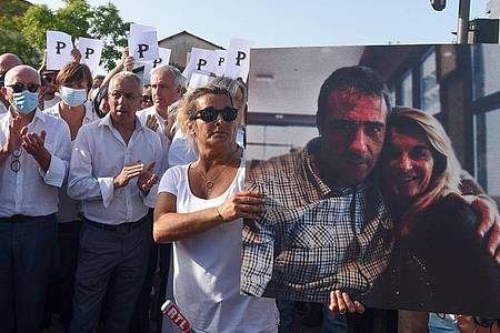 Die Ehefrau des verstorbenen Busfahrers hält während eines Protestmarsches in Bayonne ein Foto von sich und ihrem Mann. Foto: Gaizka Iroz/AFP/dpa