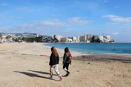 Zwei junge Frauen gehen am leeren Strand von Magaluf entlang. Foto: Clara Margais/dpa