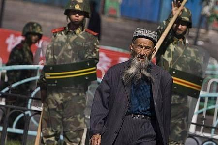 Ein Angehöriger der uigurischen Minderheit in der Unruheregion Xinjiang in Nordwestchina geht vorbei an chinesischen Sicherheitskräften. Foto: Diego Azubel/epa/dpa