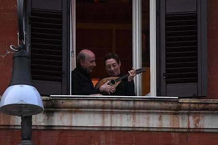 Ein Mann und eine Frau mit einem Instrument an einem geöffneten Fenster in Rom. Foto: Elisa Lingria/XinHua/dpa