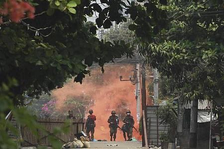 Uniformierte Soldaten mit Gewehren gehen in Yongon während einer Demonstration von Anti-Putsch-Demonstranten auf eine Rauchwolke zu. Foto: -/AP/dpa