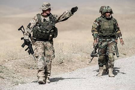 Bundeswehrsoldaten und kurdische Peshmerga Soldaten gehen in der Ausbildungseinrichtung Bnaslawa bei einer Übung am Rand einer Straße in Irak entlang. Foto: Michael Kappeler/dpa