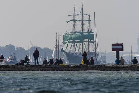 Zuschauer beobachten am Falkensteiner Strand die Windjammerparade der Kieler Woche. Foto: Frank Molter/dpa