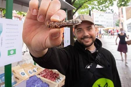 Michael Blautzik von Bugoo zeigt eine Heuschrecke auf dem Lindener Marktplatz. Der Start-up-Gründer will Menschen zur Umstellung ihres Speiseplans auf Insekten ermutigen. Foto: Julian Stratenschulte/dpa