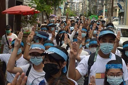 Menschen zeigen bei einer Demonstration den Drei-Finger-Gruß als Zeichen des Widerstands. Foto: -/AP/dpa
