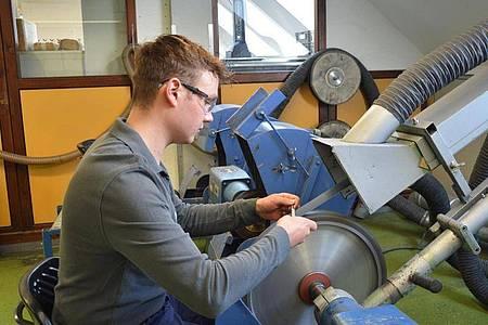 Mit Geschick und Konzentration bearbeitet Pascal Scheu an der Bandschleifmaschine die Oberfläche und Form eines medizinischen Instruments. Foto: B. Braun Melsungen AG/dpa-tmn