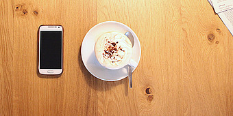 Smartphone und Kaffeetasse