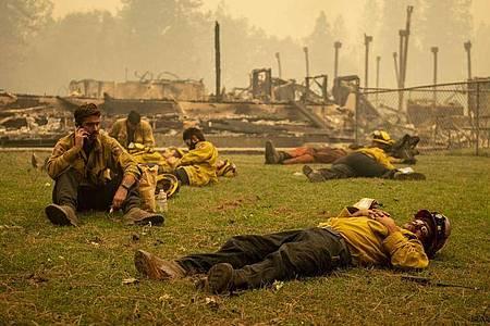 Eine Feuerwehrmannschaft macht eine Pause neben einer Schule in Berry Creek in Nordkalifornien, die durch ein Feuer zerstört wurde. Verheerende Waldbrände wüten weiter entlang weiten Teilen der US-Westküste. Foto: Jason Pierce/Sacramento Bee via ZUMA Wire/dpa