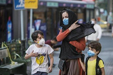 Kinder mit Gesichtsmasken gehen mit ihrer Mutter eine Straße entlang in Teheran. Der Iran hat nun Bußgelder bei Verstößen gegen die Corona-Regeln eingeführt. Foto: Ahmad Halabisaz/XinHua/dpa
